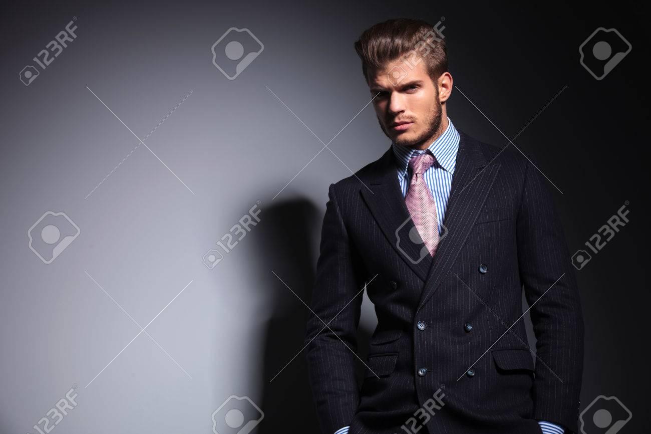 Banque d images - Détendue jeune homme de mode en costume-cravate debout  les mains dans les poches et en regardant la caméra sur fond gris 3b5bf706464