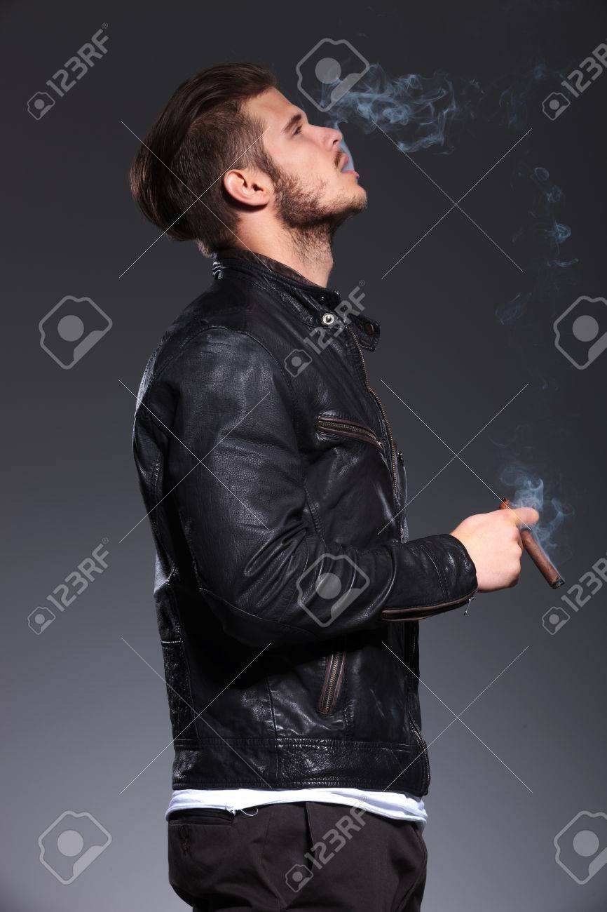 Side View Of A Young Man In Leather Jacket Smoking And Blowing