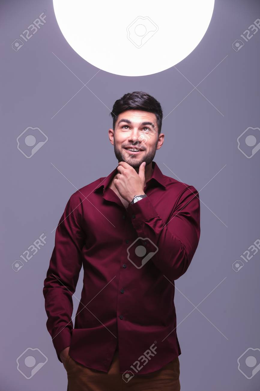 pensive smiling young casual man looking into a big ball of light above his head, wondering about it Stock Photo - 25033950
