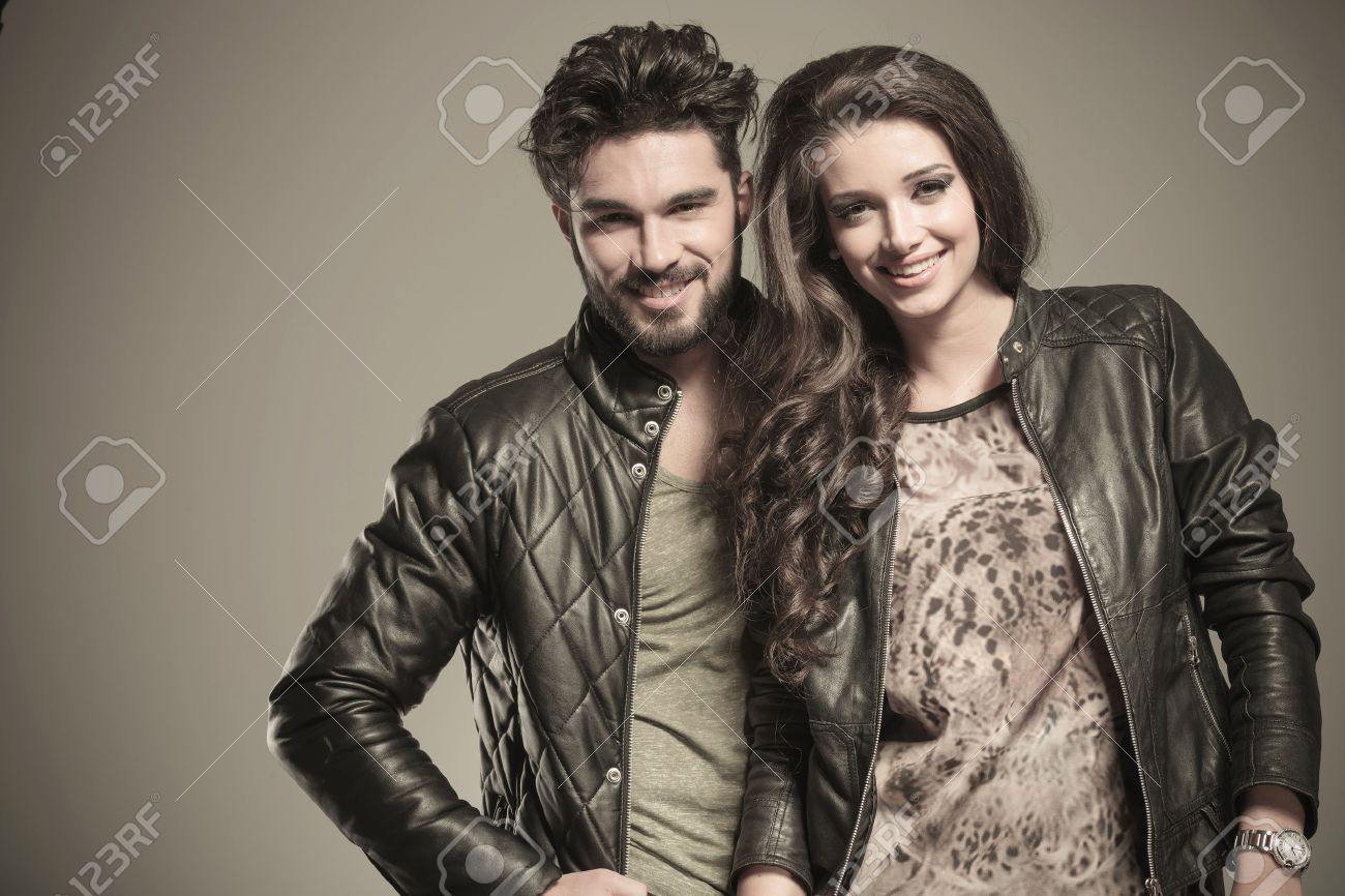 happy fashion couple in leather jackets smiling to the camera in studio Stock Photo - 25307597