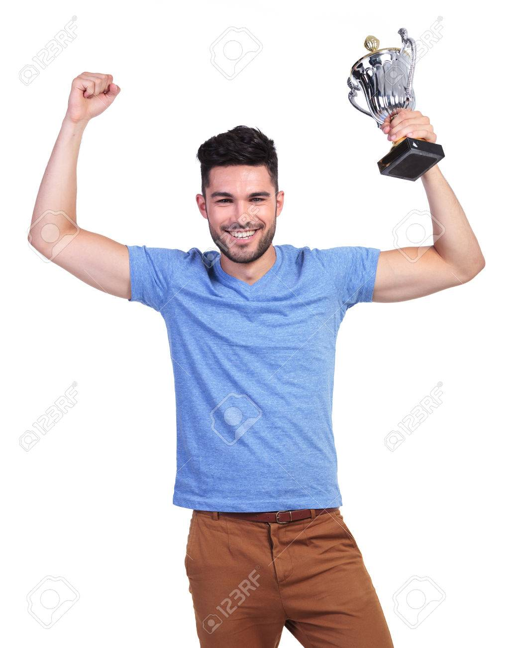 Winning Young Casual Man With A Big Trophy Cup And Hands In The
