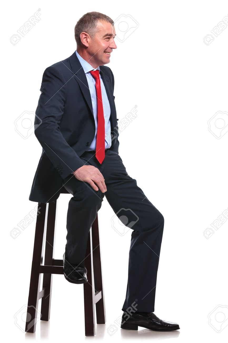 Man sitting in chair side - Mid Aged Business Man Sitting On A Chair And Smiling Away From The Camera Isolated