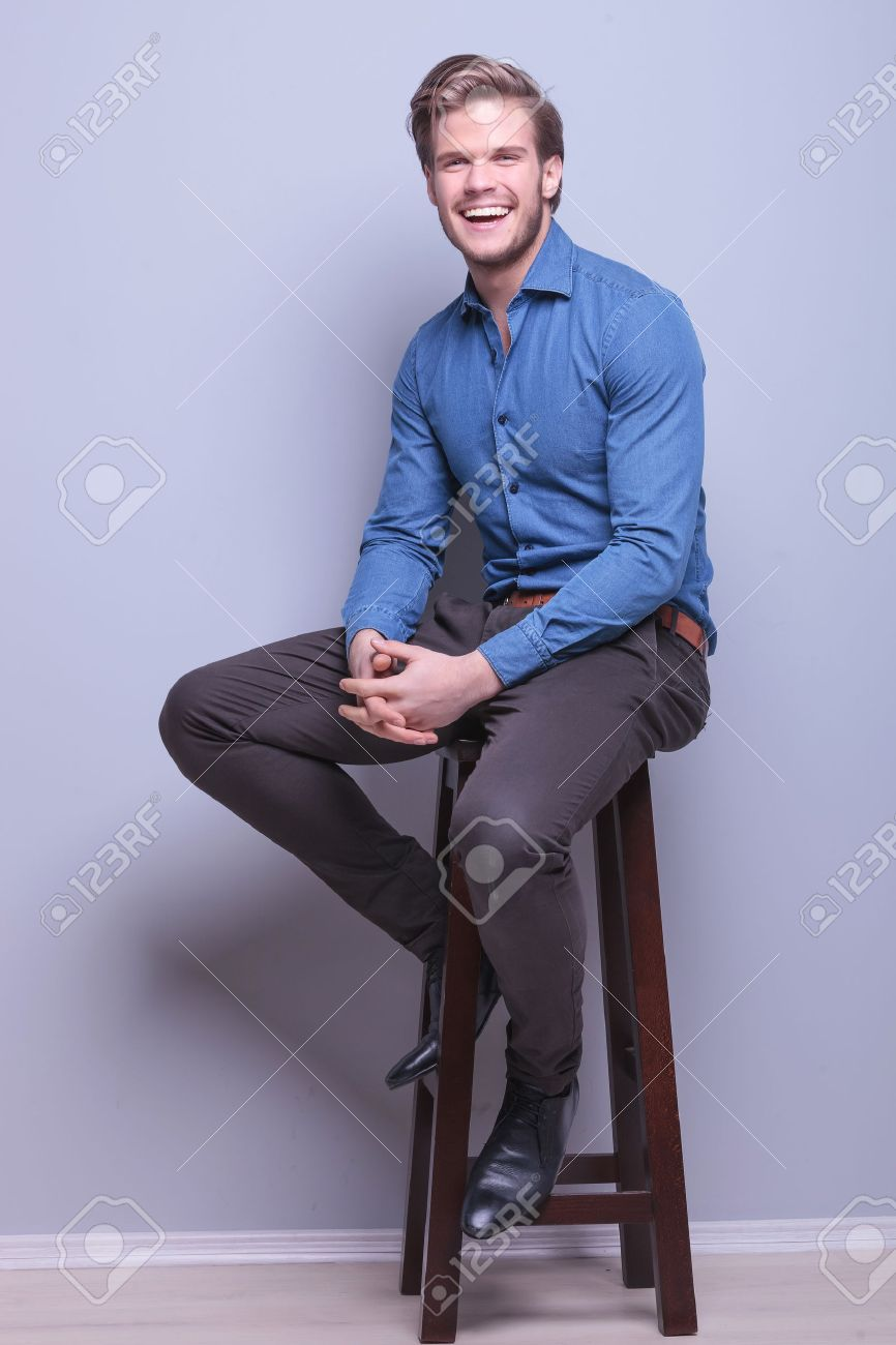 Man sitting in chair side - Laughing Young Casual Man Sitting On A High Chair In Studio Stock Photo 28104995