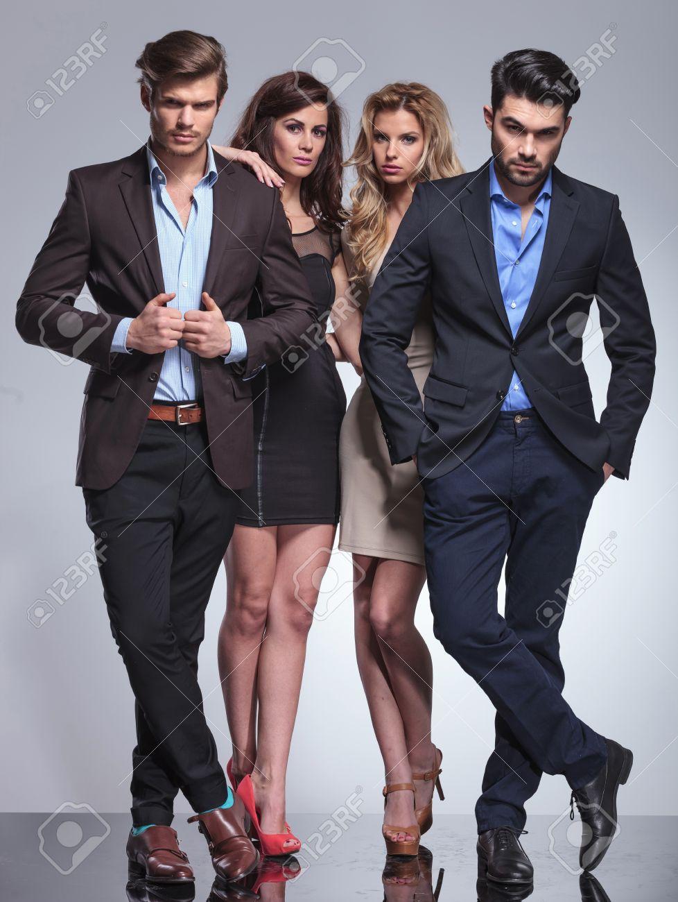 Las Mujeres Elegantes De Pie Detrás De Sus Hombres Y Posar En El