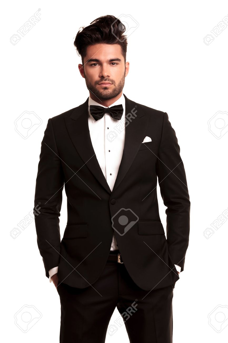 fc379bb9f5d97 Stock Photo - stylish man in elegant black suit and bowtie standing with  hands in pockets on white background