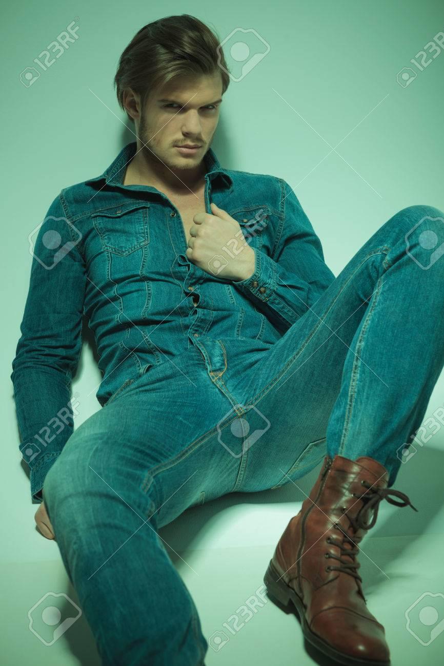 more photos fb854 63aa4 Hot moda uomo disteso sul pavimento, appoggiandosi su un muro mentre si  tira la camicia di jeans. Guardando alla macchina fotografica.