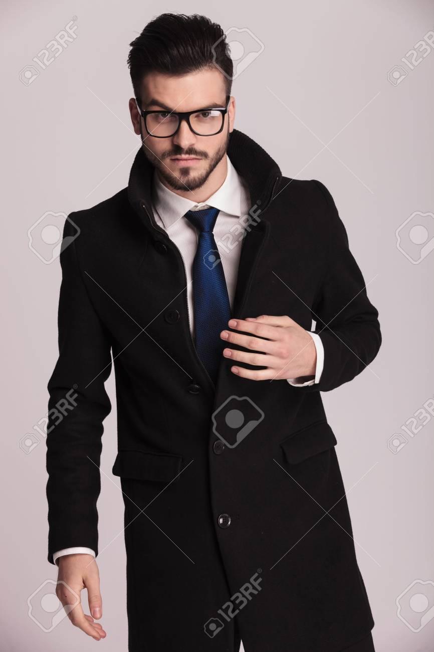 style actuel choisissez le dégagement grande remise de 2019 Attractive jeune homme d'affaires portant un long manteau élégant en  regardant la caméra tout en maintenant une main sur son manteau.