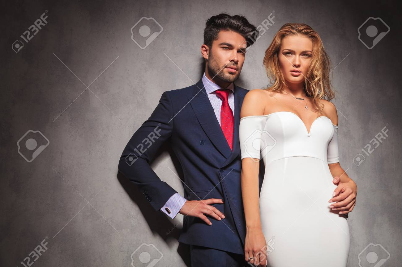 young elegant fashion couple looking away from the camera in studio, while standing with hands on hips, man holding his woman by her waist - 46720285