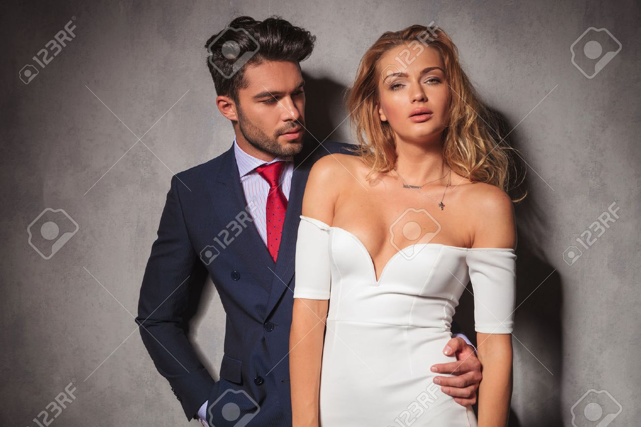 85677bc94 Foto de archivo - Joven hombre elegante y guapo en traje y corbata mira a  su mujer rubia de vestido blanco