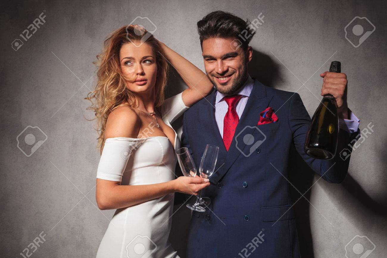 man holding a bottle of champagne saying cheers with his woman next to him. hot fashion couple ready to celebrate - 46720356