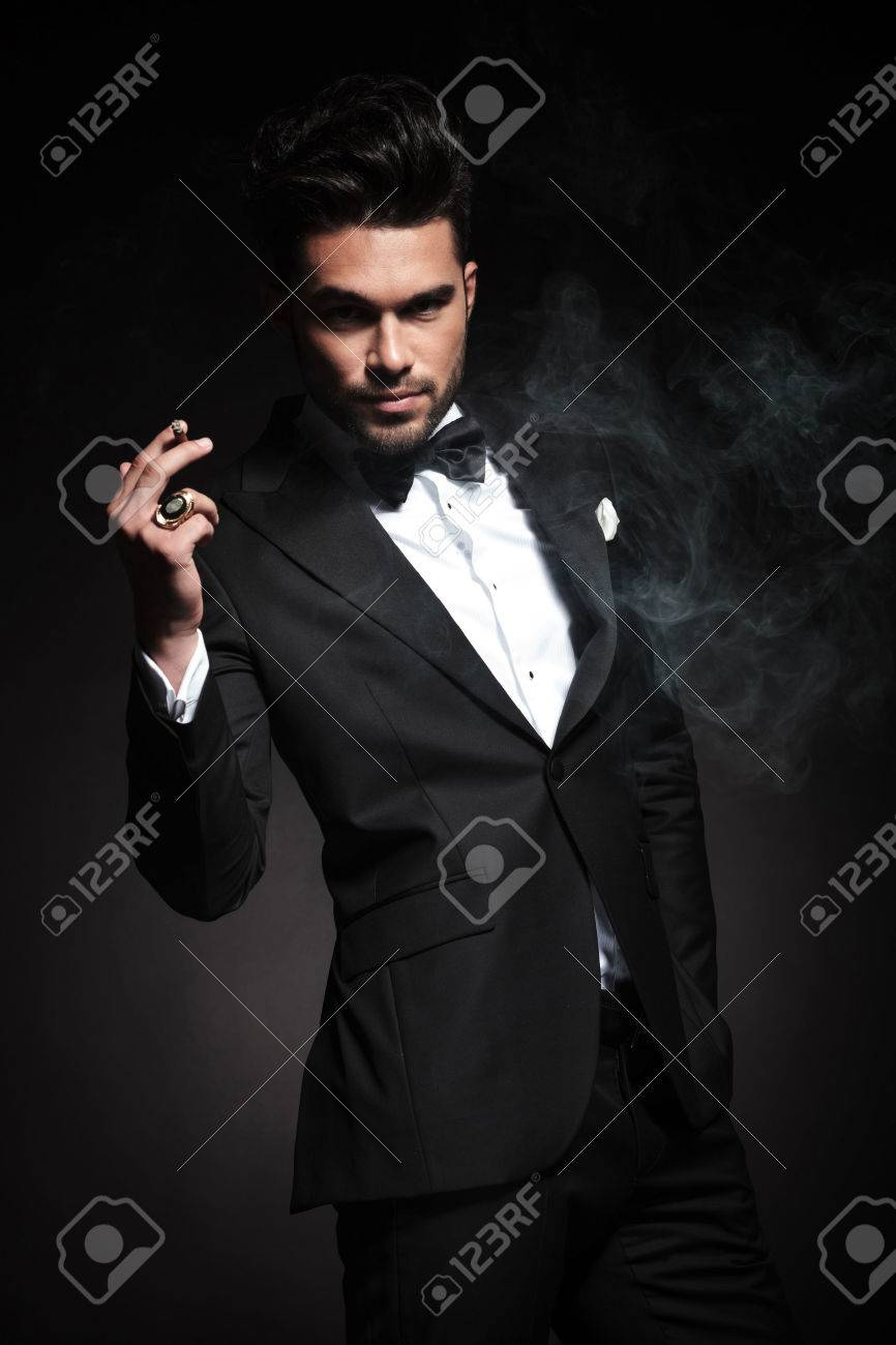 Handsome young business man enjoying a cigarette while holding one hand in his pocket. - 47359641