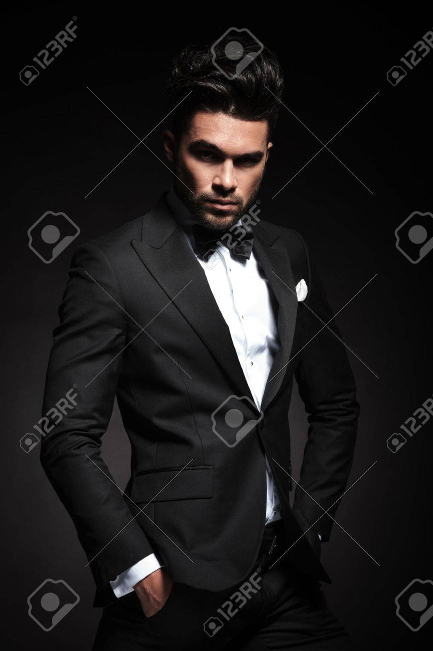 Attractive young business man looking at the camera while holding both hands in his pocket. - 47359655