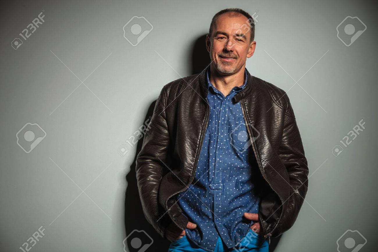 smiling old casual man in leather jacket with hands in pockets standing against gray studio wall - 47850739