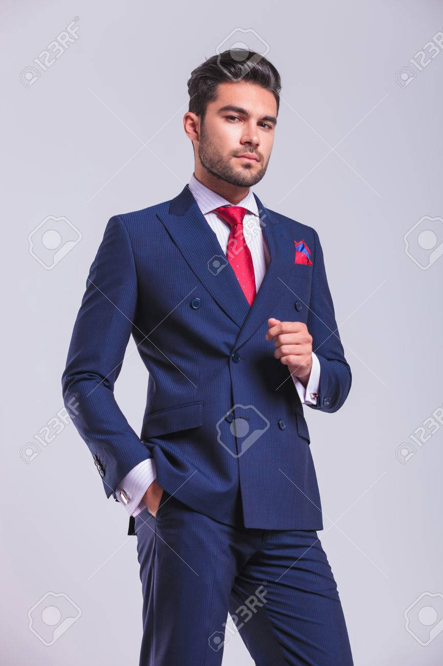 young man in elegant suit standing in studio posing with hand in pocket - 48480913