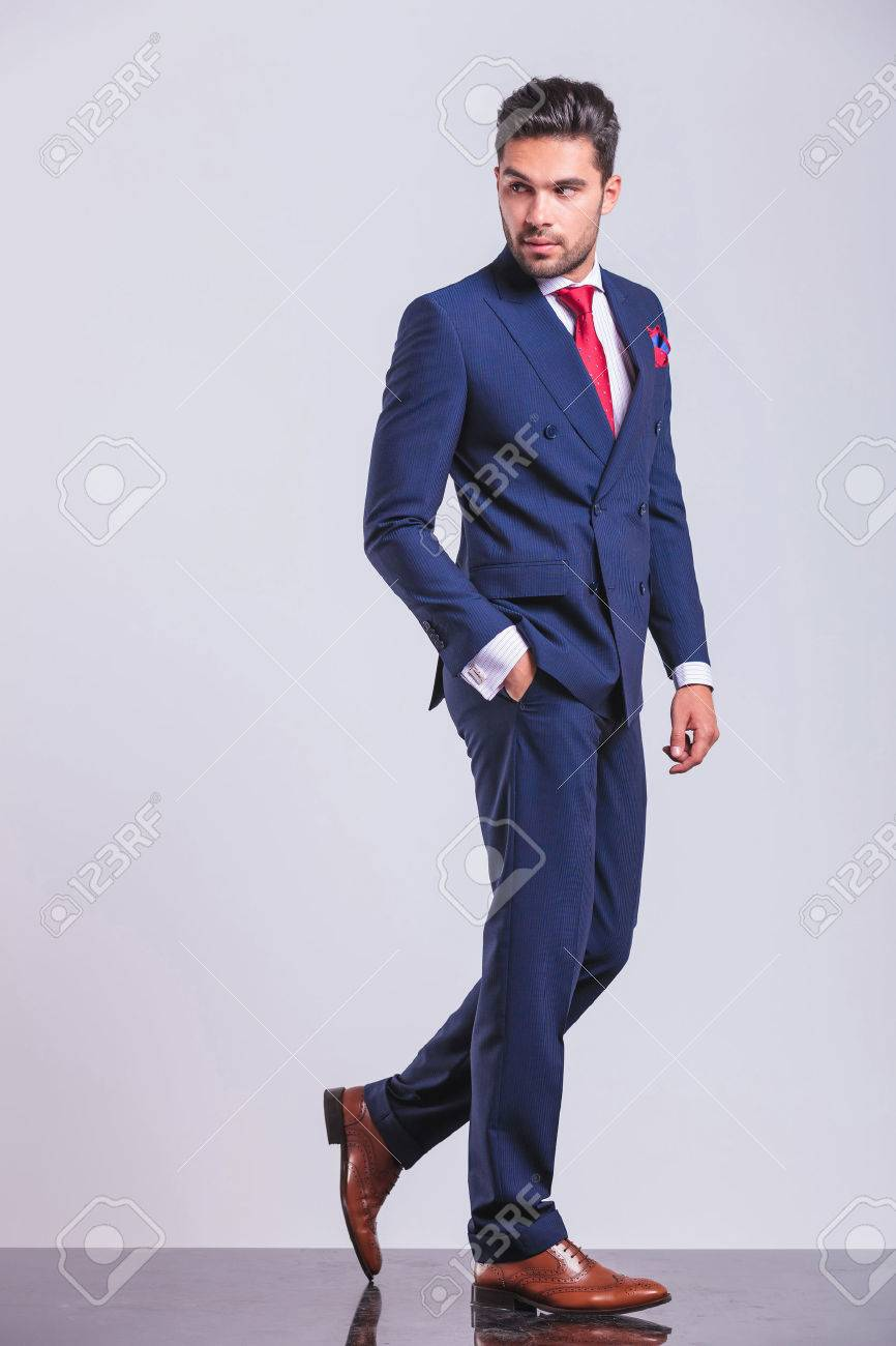 man in business suit walking while looking away with hand in pocket - 48480928