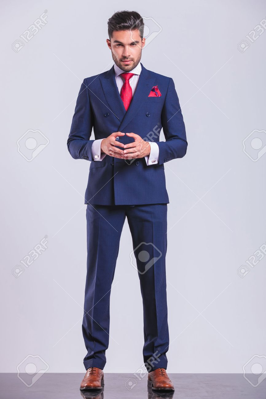 confident handsome business man posing while standing and touching his palms - 48480935