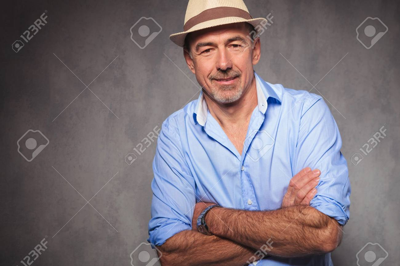 7ed784e6025 portrait of old man posing in studio background wearing a hat while looking  at the camera