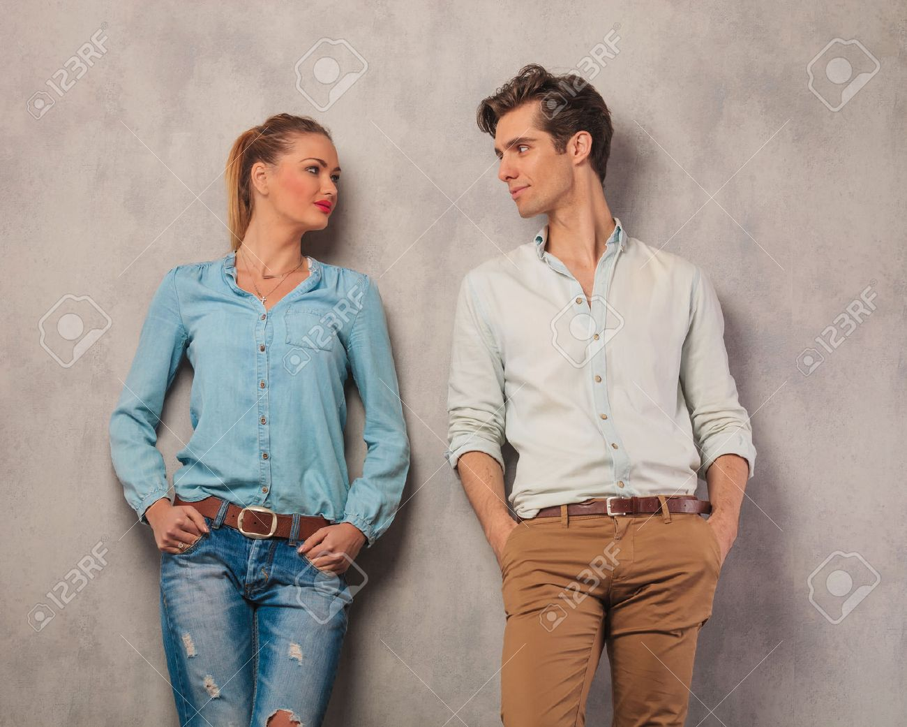 young couple looking at each other with hands in pockets in studio background - 51507838