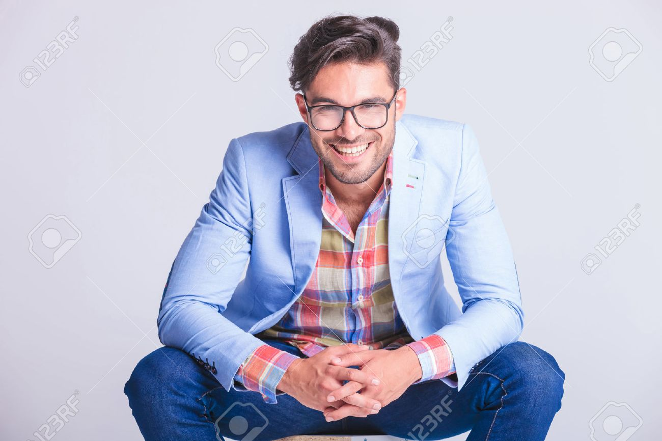 close portrait attractive man posing seated with legs spread open and hands touching, while smiling at the camera in studio background - 52312760