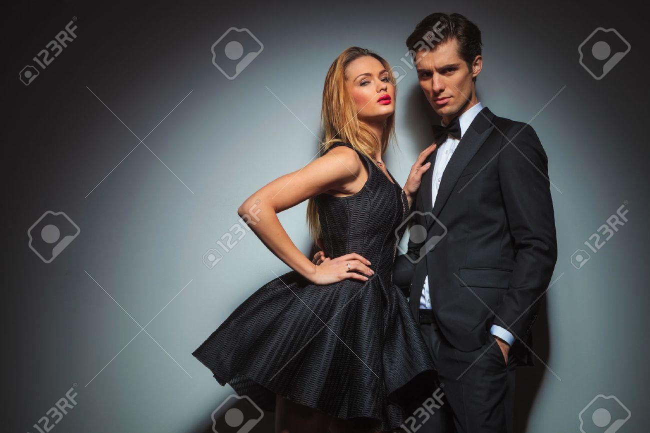 elegant couple in black posing together in gray studio background. - 54205240