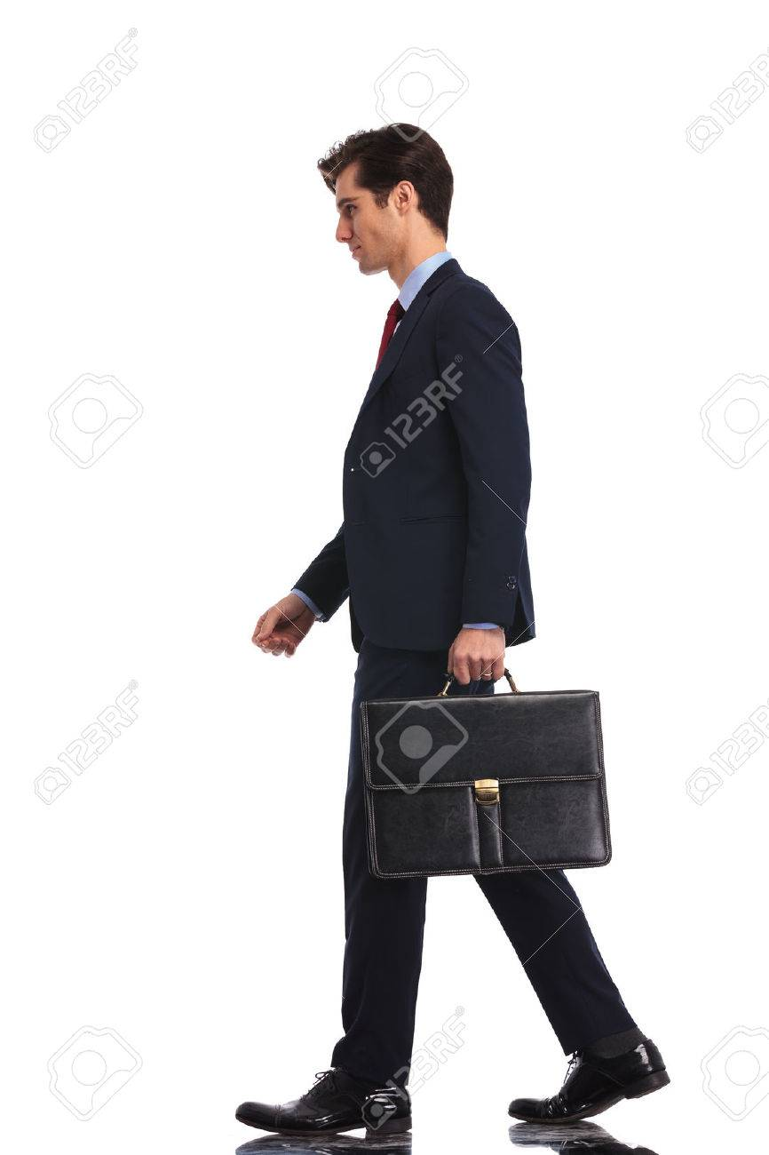 full body picture of a young business man walking forward and holding a briefcase, isolated on white background - 64558466