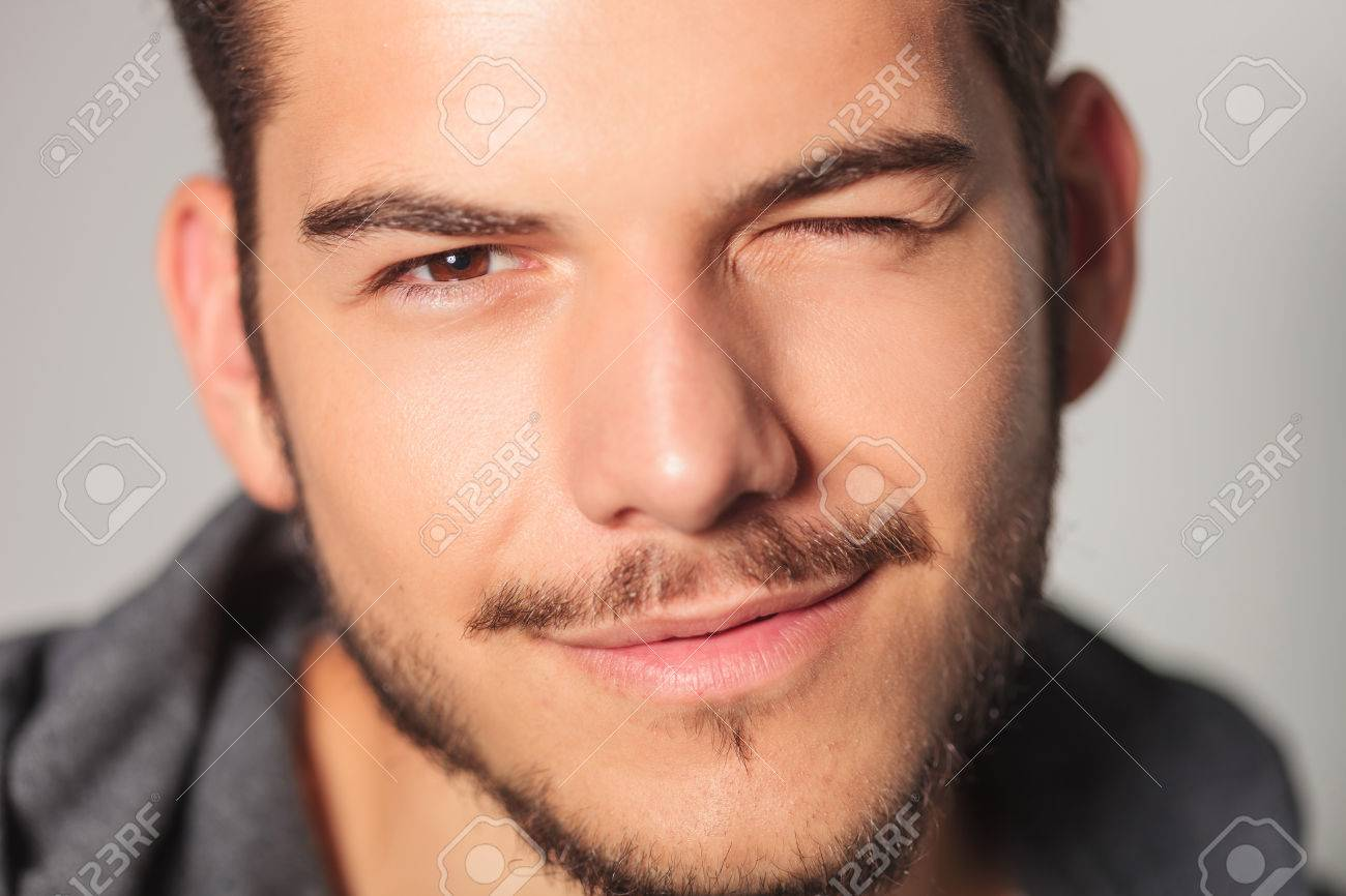 smilling young man is winking his eye , closeup picture in studio - 64558605