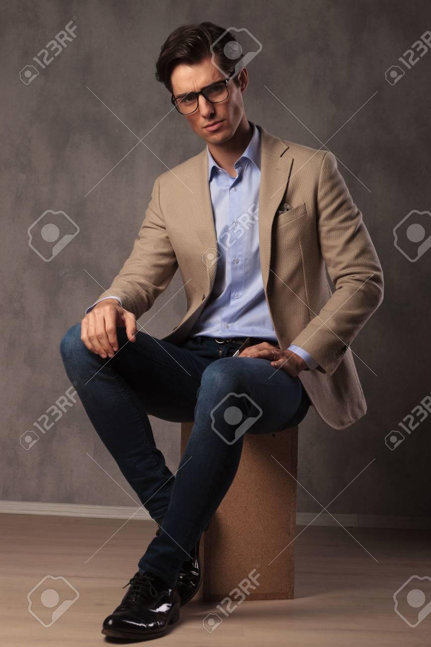 Homme élégant Cool Assis En Studio, Portant Un Jean Et Un
