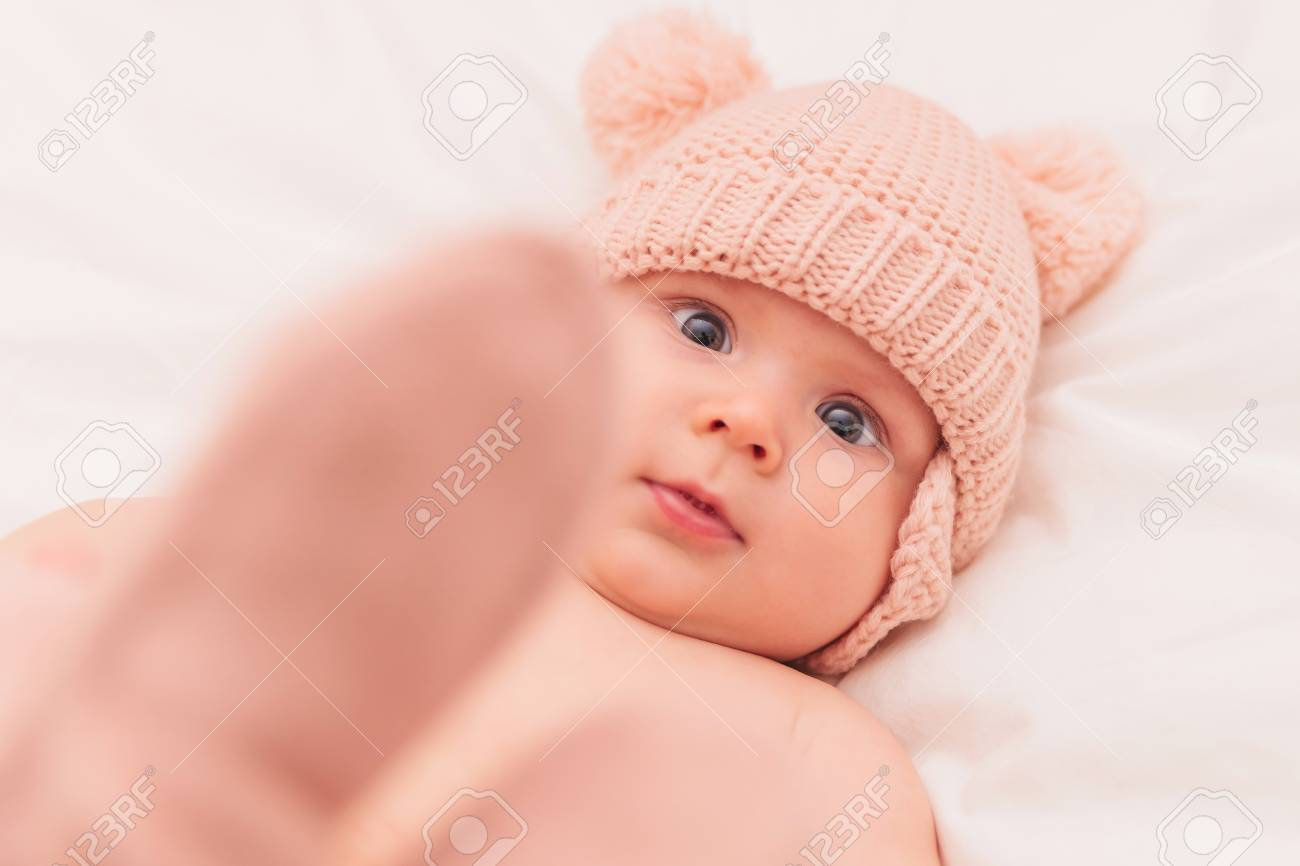 0c5fda06fbf2 adorable 5 months old baby girl wearing knitted hat and hold her feet up  and looks