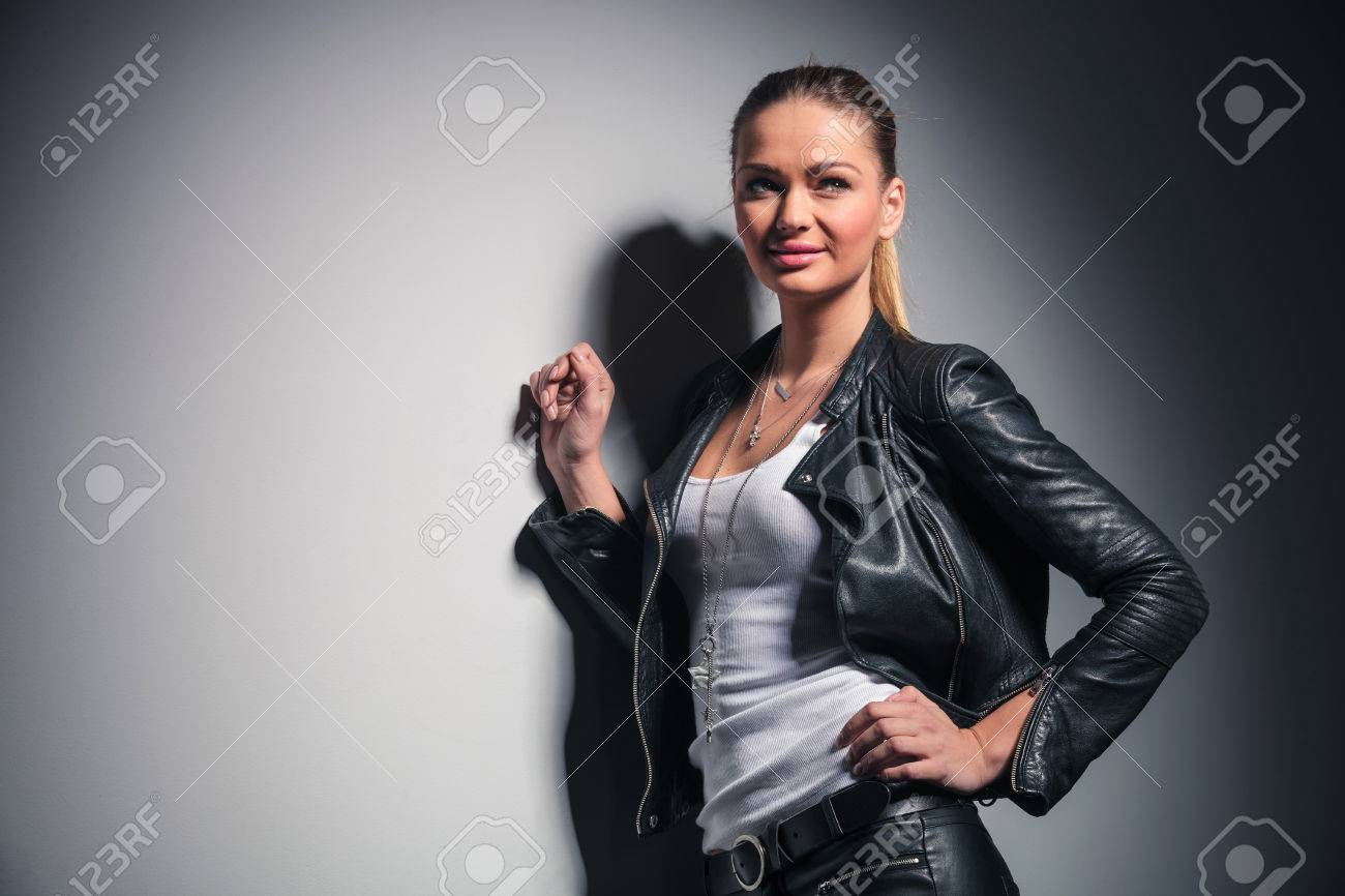 happy young blonde woman in leather clothes leaning on grey wall