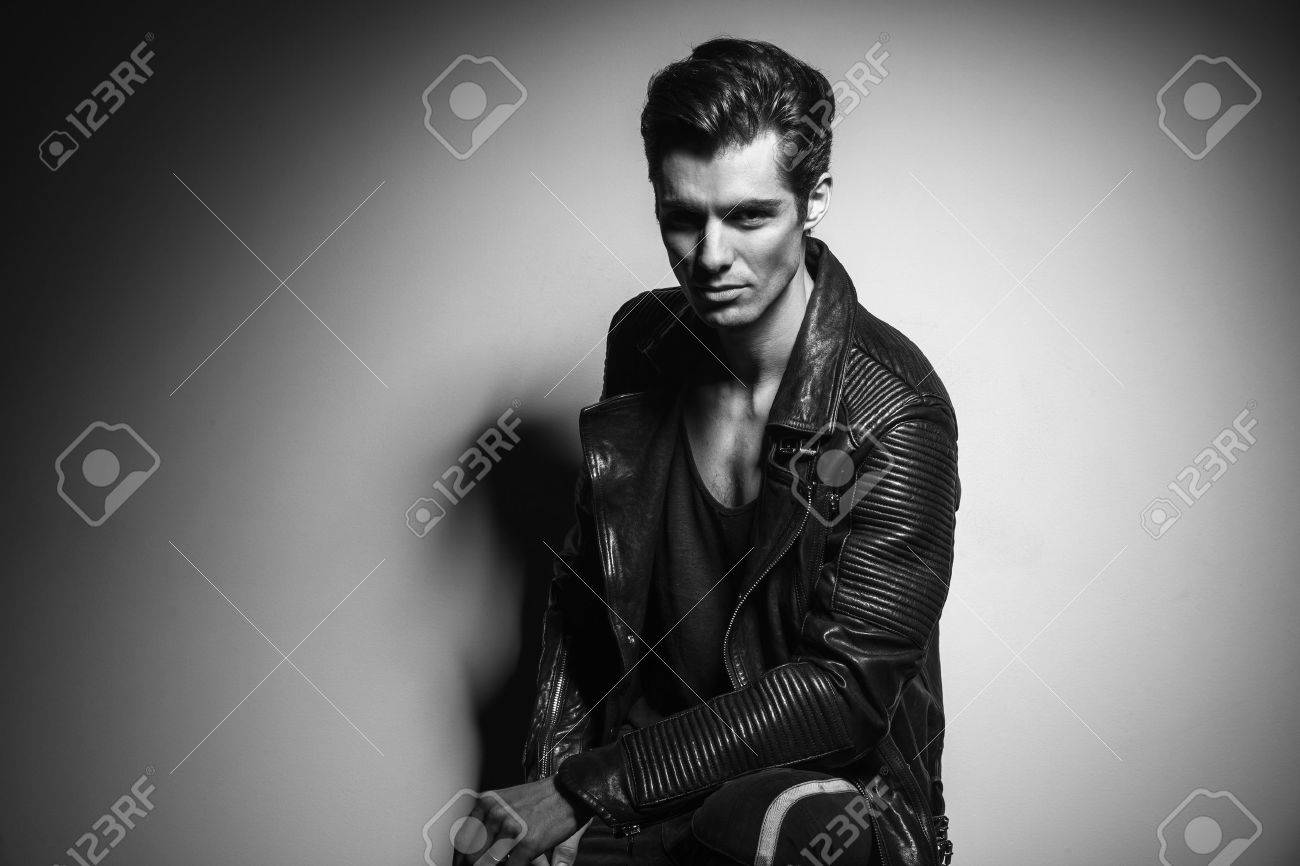 Relaxed Young Man In Leather Jacket Sitting And Leaning Elbow