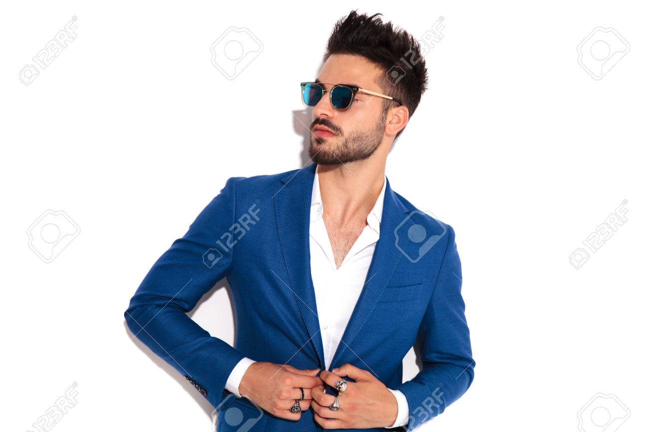 elegant man wearing sunglasses buttoning his suit and looks away to side on white background - 80997671