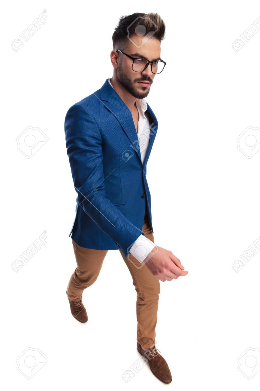 a77e93ccd1e9 confident smart casual man walking to side on white background, full body  picture Stock Photo