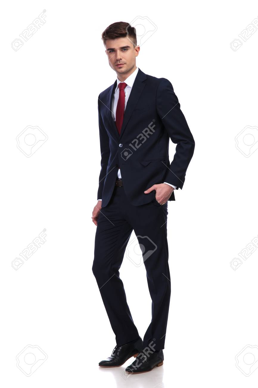 6581a4c70ea0 confident young businessman wearing a navy suit and a red tie, standing and  posing with