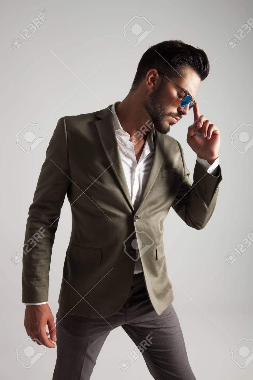 367c060c84a2 pensive man with green suit and sunglasses looks down to side whlie  standing on light grey