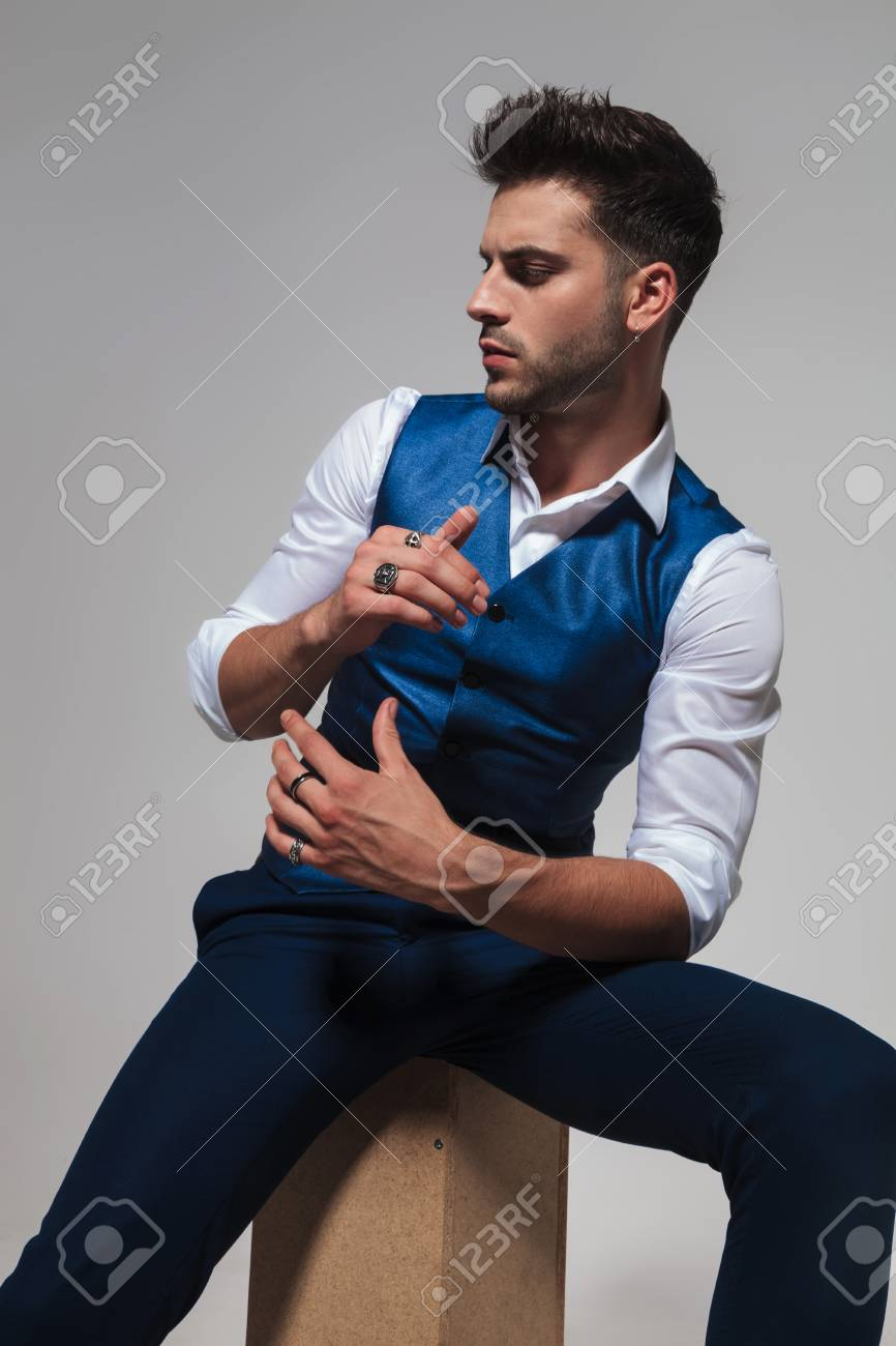 fe10b2840592 portrait of stylish man wearing a blue waistcoat sitting on a wooden box  and looking down