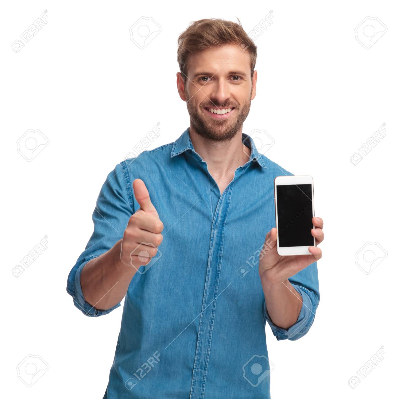 smiling casual man showing the blank screen of his phone and makes the ok sign on white background - 107378817