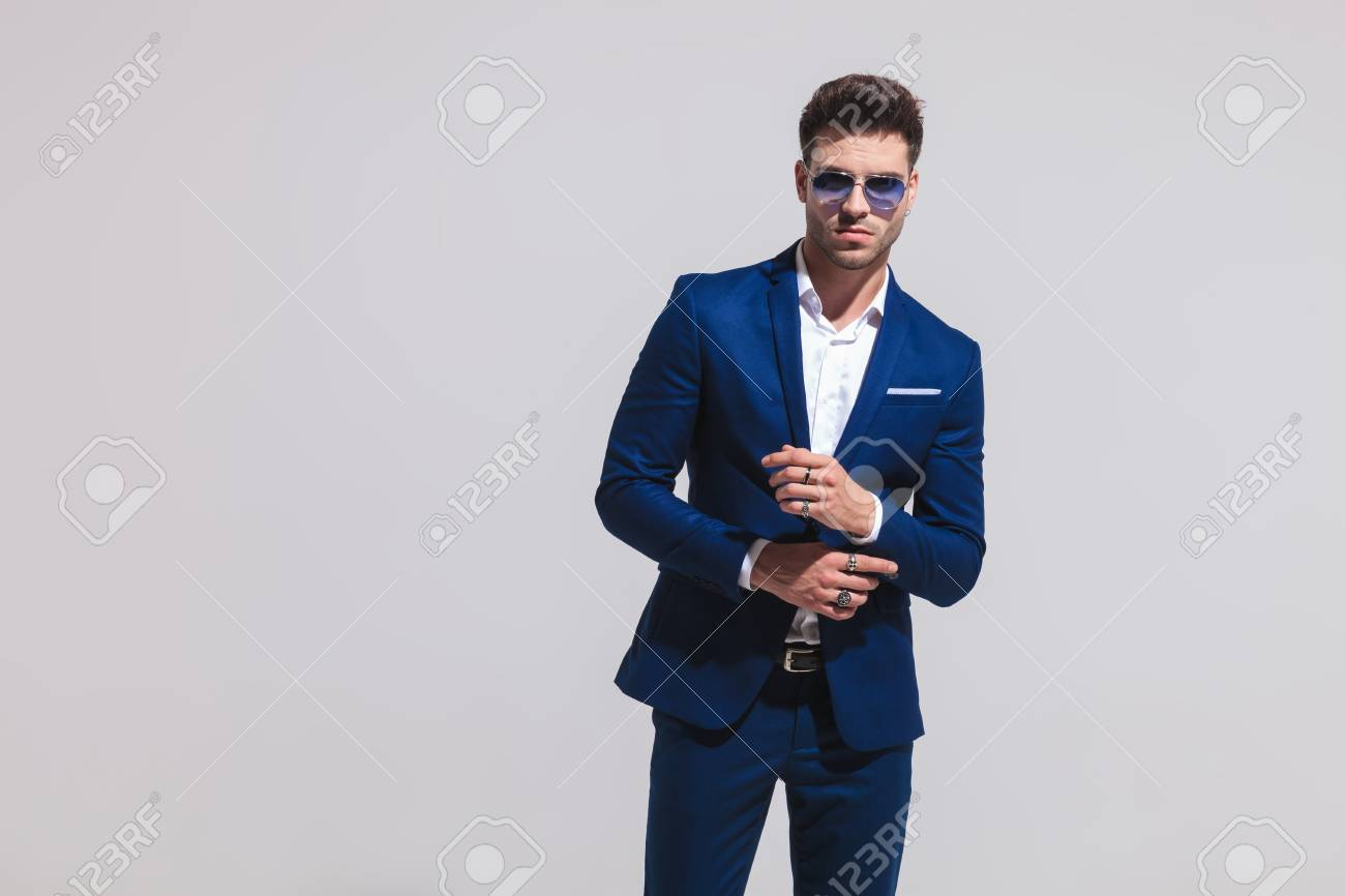 b991e7bda5e4 fashion sexy man in suit and sunglasses fixes his sleeve on grey background  Stock Photo -