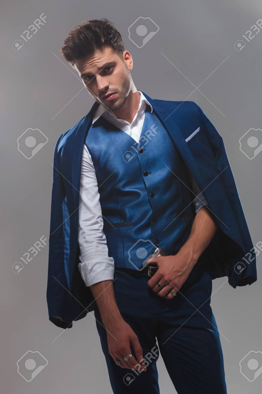 portrait of classy man wearing a blue suit holding belt while..