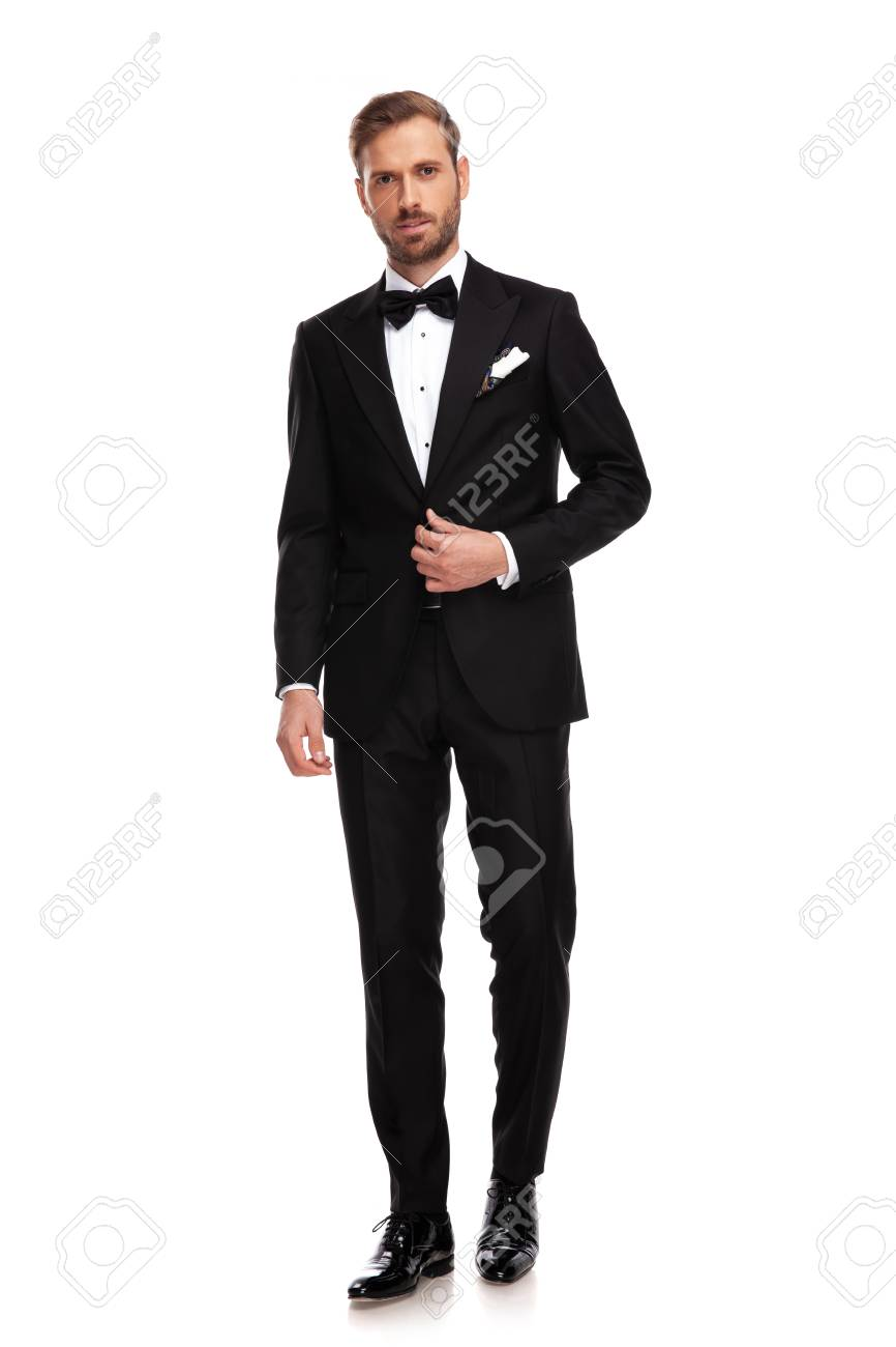 handsome businessman standing on white background and buttoning black suit - 115180493
