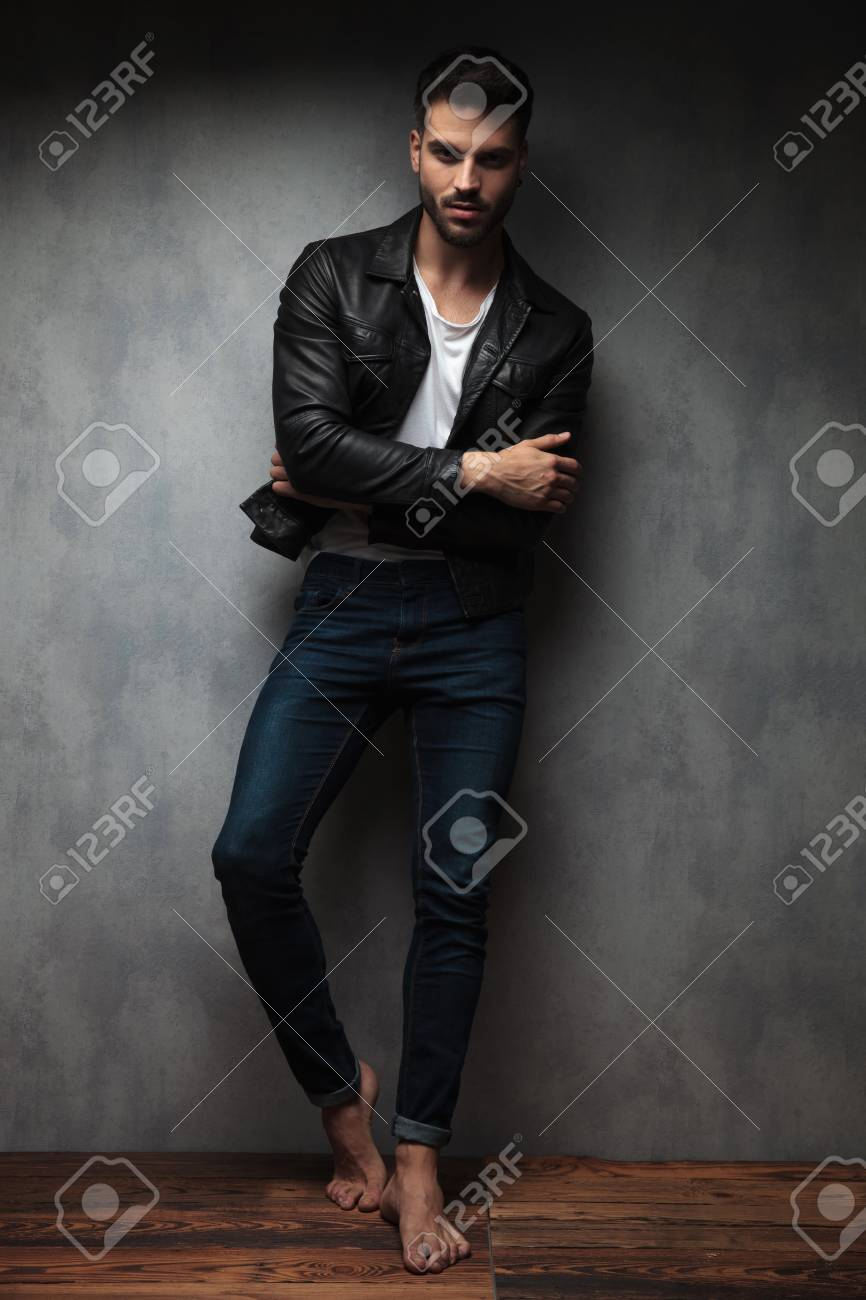 cool young man standing with hands crossed and feet, leaning against studio wall - 117535498