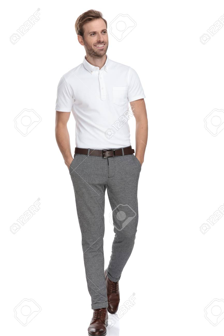 curious man with hands in pockets walks and looks to side on white background - 117535994
