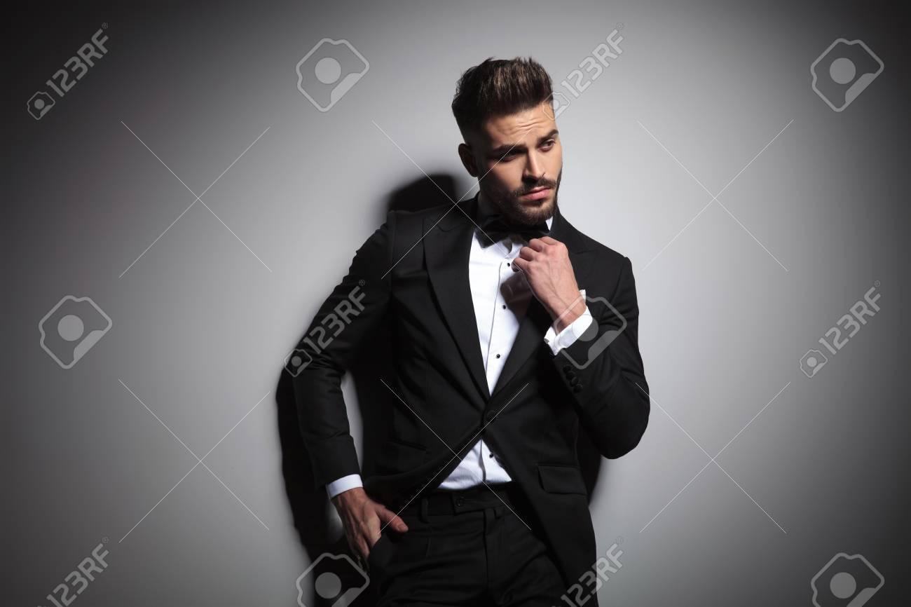 caucasian guy in black tuxedo adjusting bowtie on gray background - 121916211