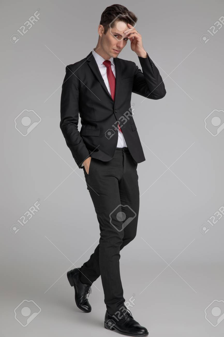 handsome man in black suit stepping and thinking with hand in pocket and at forehead on grey background - 121916728