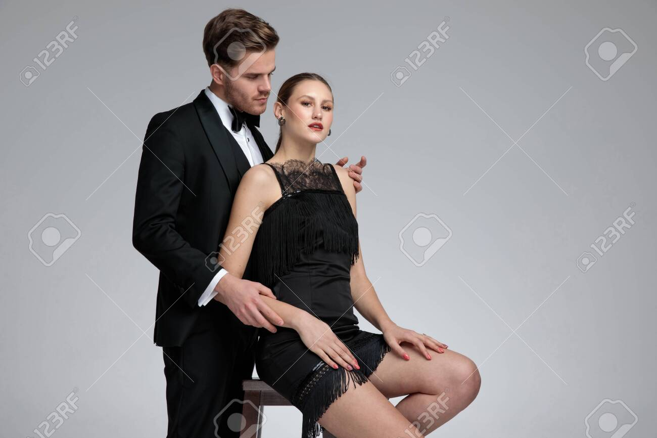 Handsome young man dressed in a tuxedo standing and embracing his girlfriend from behind while she is sitting on chair with her arms on her legs on gray studio background - 124543820