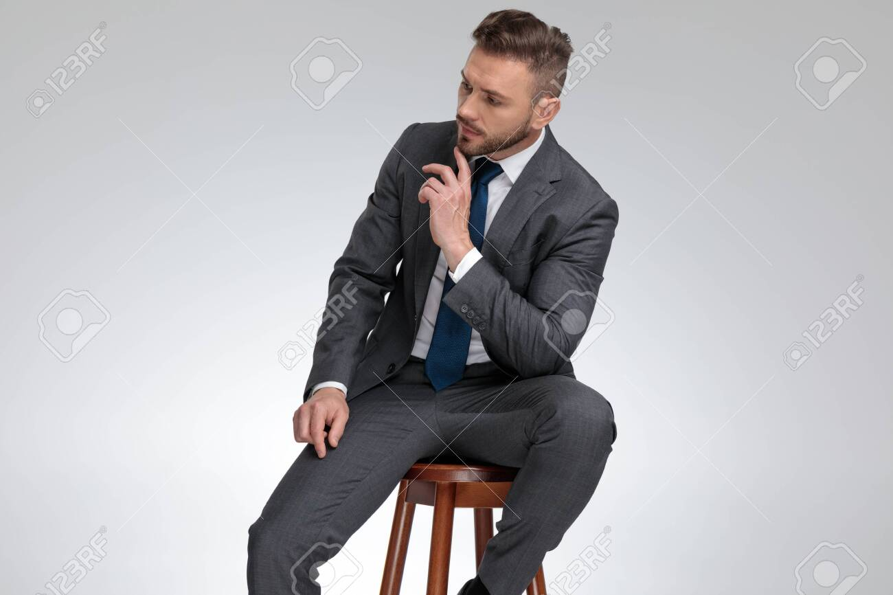 pensive young businessman sitting on stool and wonders about something on grey background - 129386657