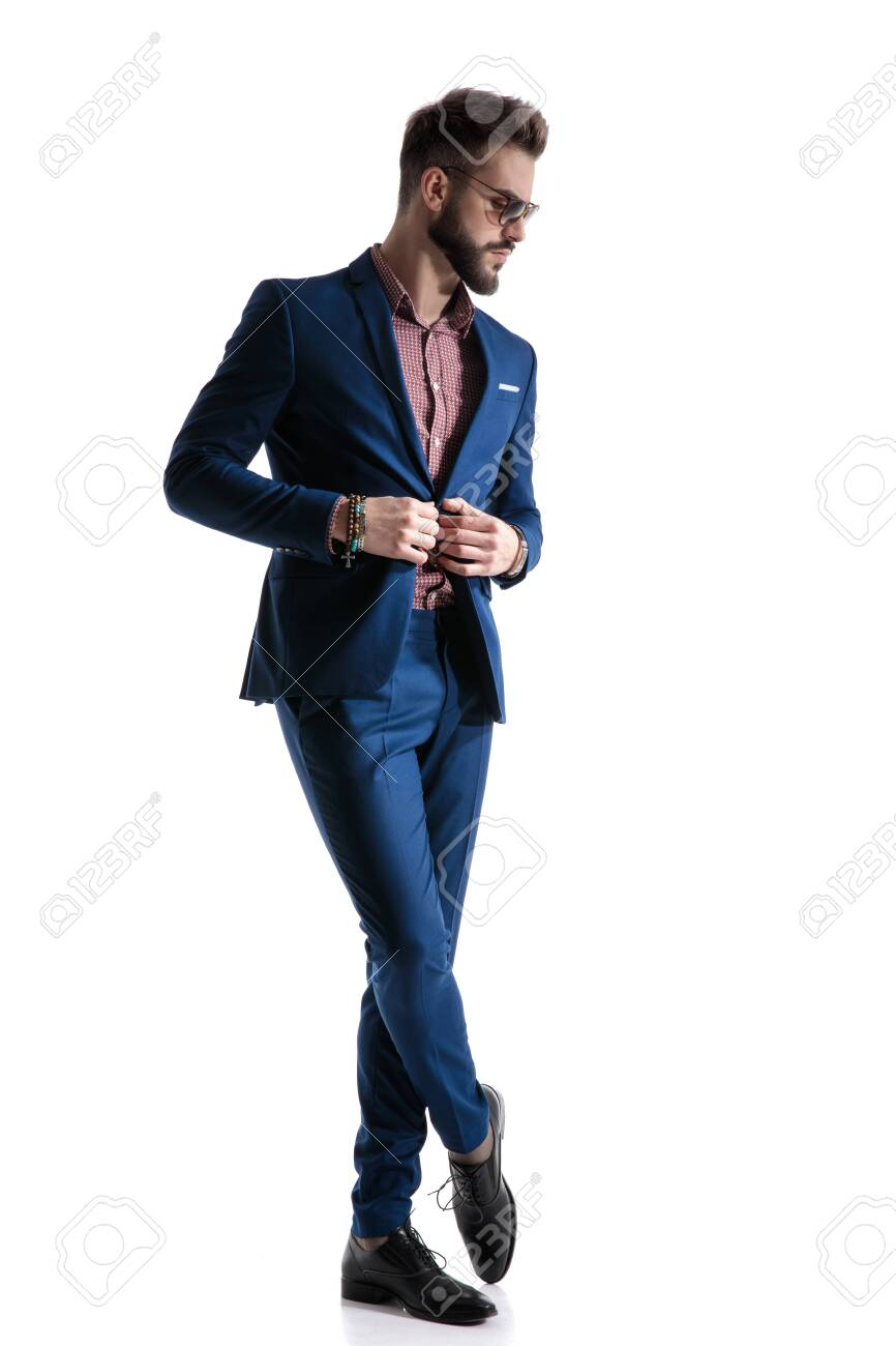 gorgeous formal business man in blue suit with beard and sunglasses is standing with legs crossed and fixing his jacket while looking down pensive on white studio background - 130341939