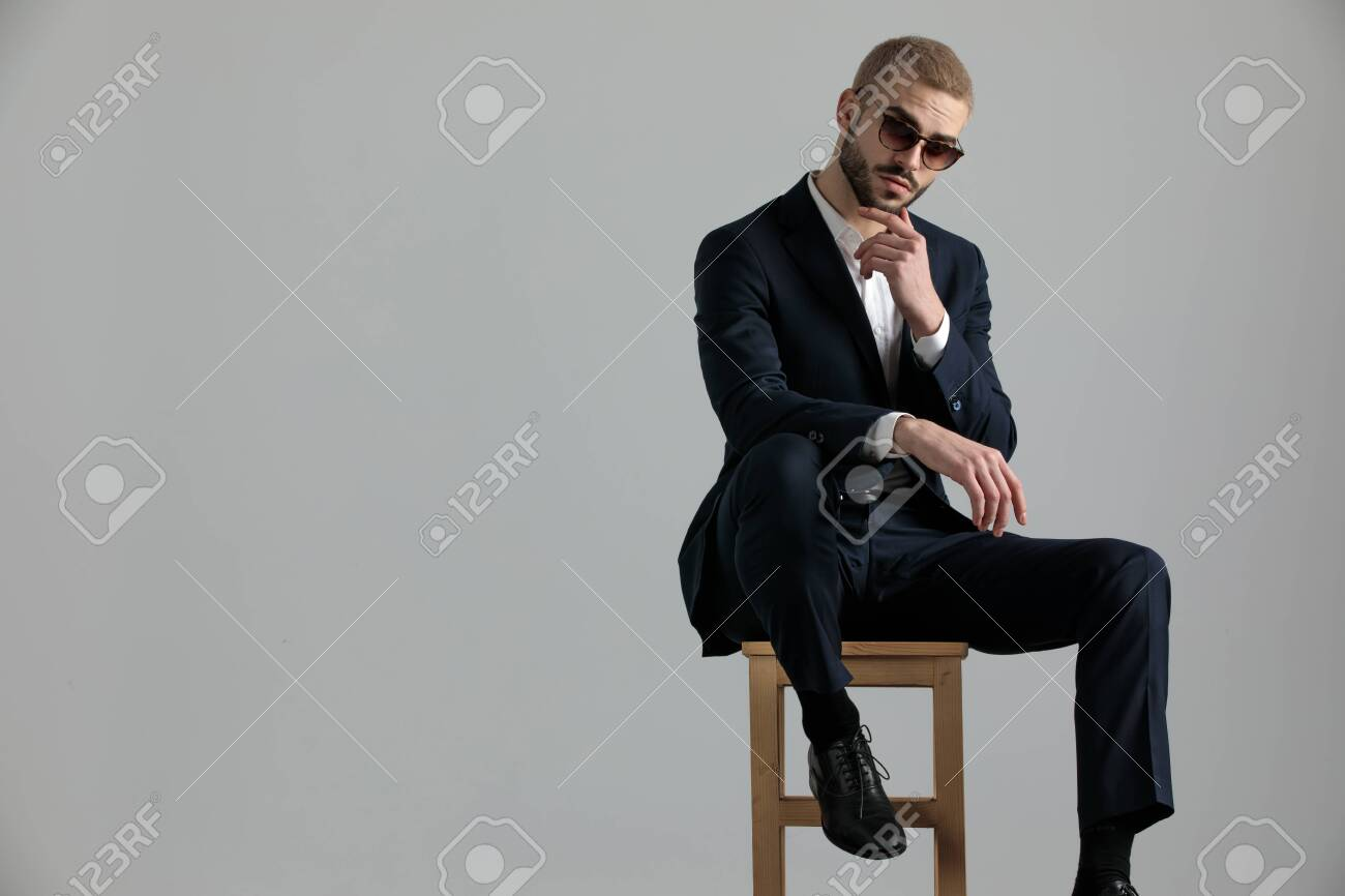 handsome formal business man wearing a navy suit and sunglasses sitting with one leg resting on a chair and touching his chin while looking at camera pensive on gray studio background - 130802330