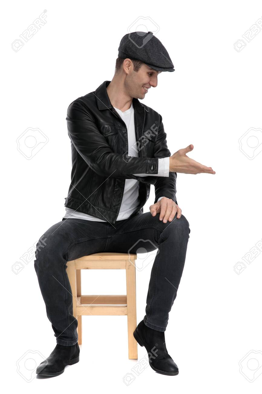 good looking casual man wearing a black leather jacket and hat sitting and presenting to a side happy while looking down against white studio background - 130803292