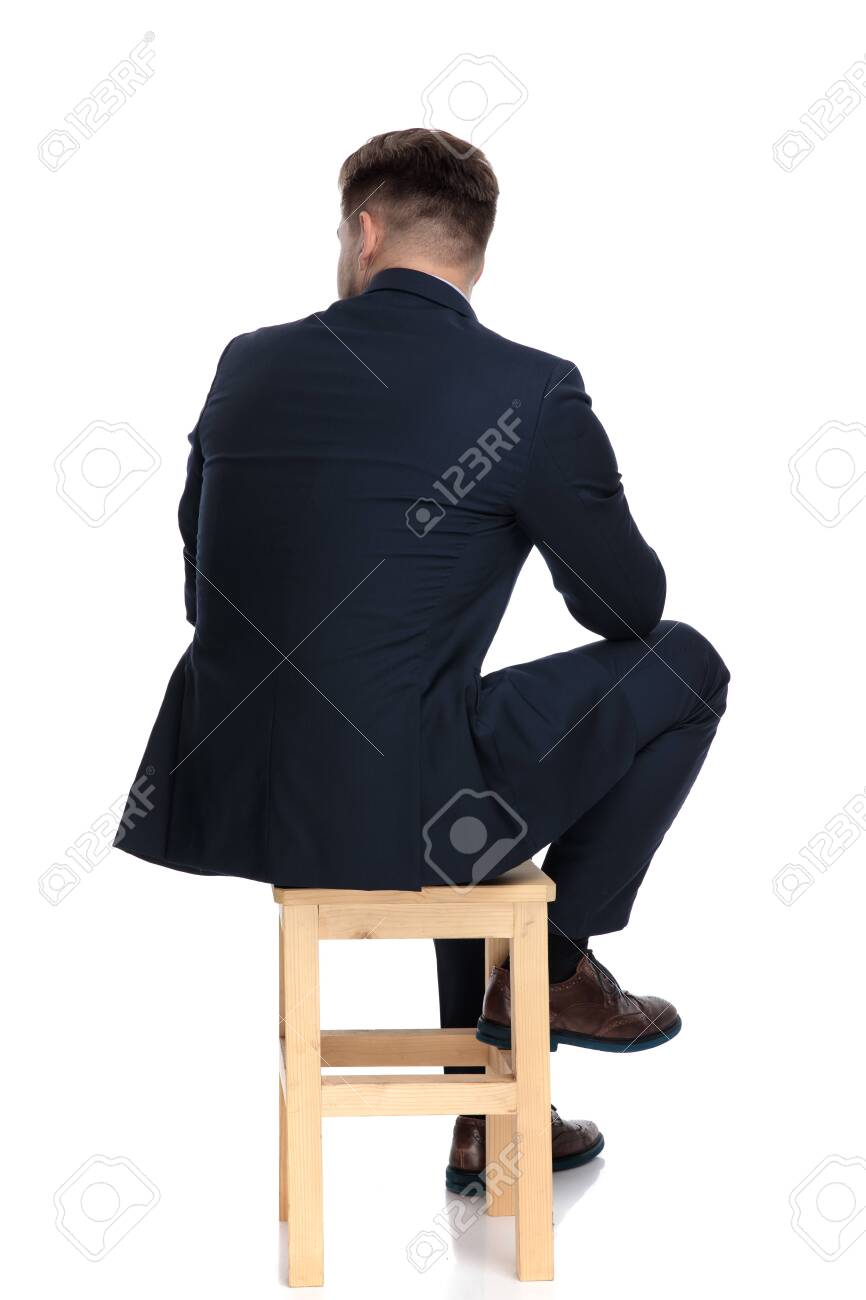 back view of young businessman looking to side and thinking, sitting isolated on white background in studio - 130804209