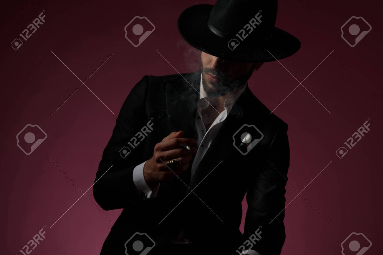 Thoughtful man smoking and looking away while wearing a black suit and hat, sitting on cherry-colored studio background - 132282175